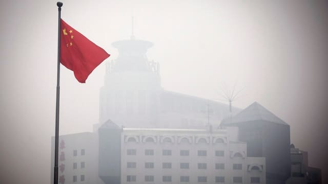 Eine chinesische Fahne weht im Smog, dahinter ist eine Gebäude zu sehen.