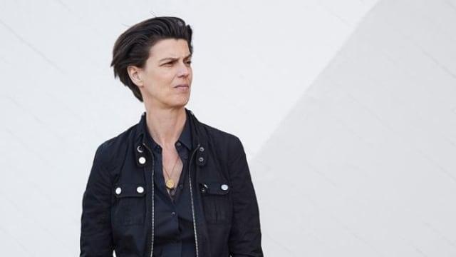 Carolin Emcke trägt eine schwarze Jacke. Sie steht vor einem weissen Hintergrund.