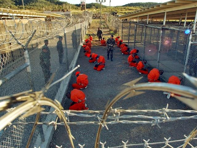 Zahlreiche Gefangene in orangen Overalls knien auf dem Erdboden.