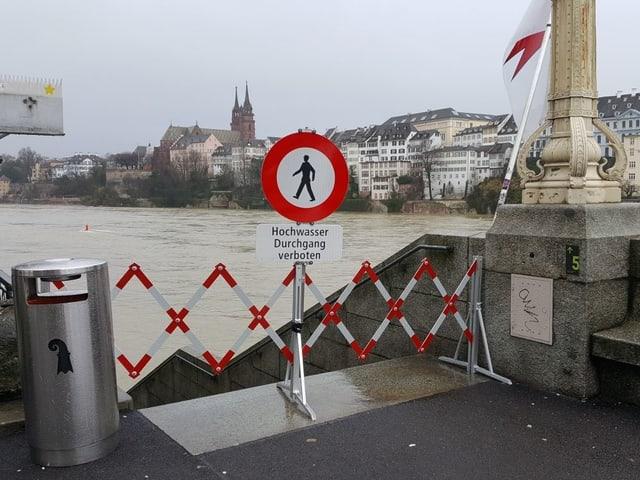 Vor einer Treppe steht rotweisse Schranke mit eine Verbotsschild für Fussgänger. Im Hintergrund sieht man den brauen Rhein und das Basler Münster.