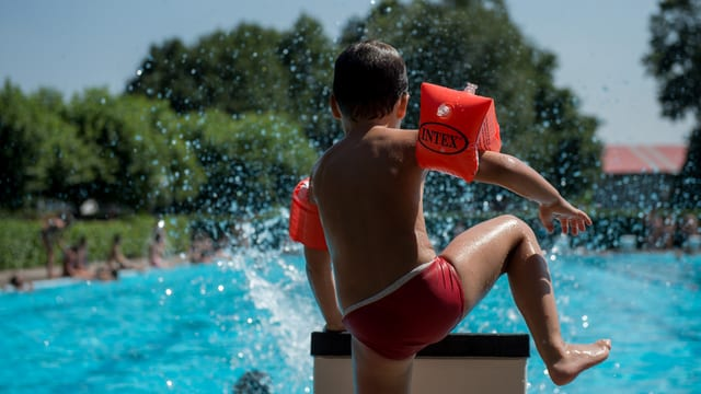 Ein Junge steigt auf den Beckenrand eines Freibads.