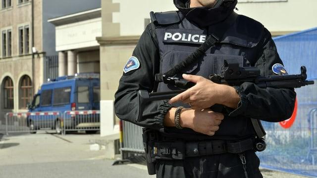 Genfer Polizist mit Schutzweste und Maschinenpistole in der Nähe eines Gerichtsgebäudes