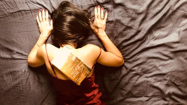 Annette König liegt auf einer Unterlage und stemmt das Buch «Lästige Liebe» von Elena Ferrante in die Höhe