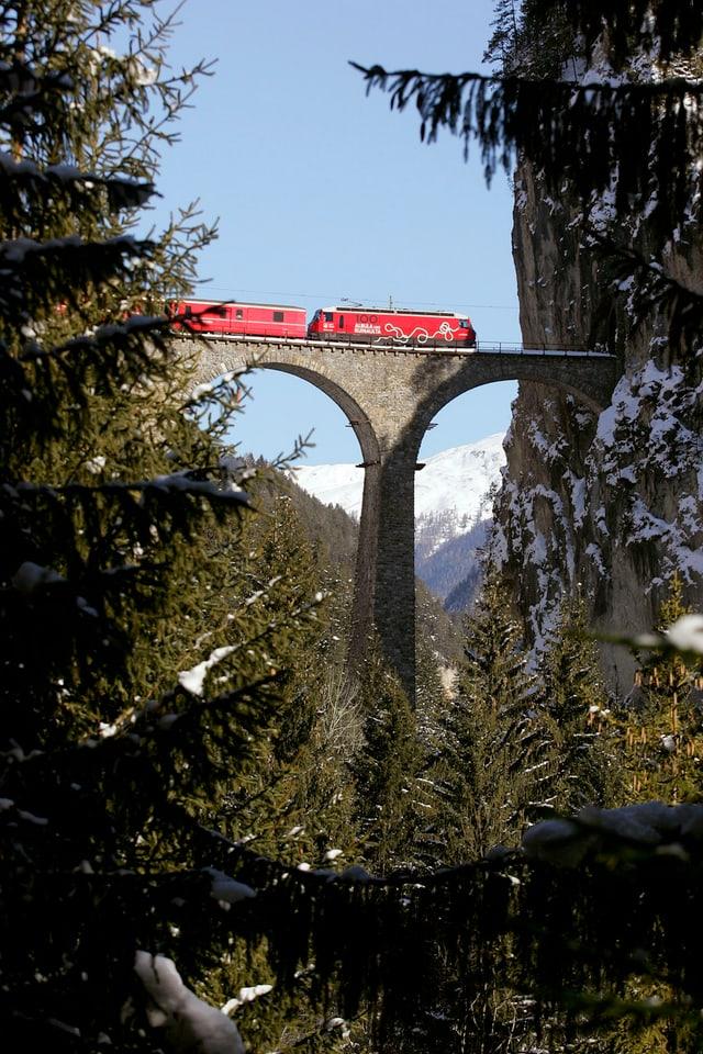 Ein roter Zug der Rhätischen Bahn überfährt das Landwasserviadukt auf der Albulalinie nahe Filisur.