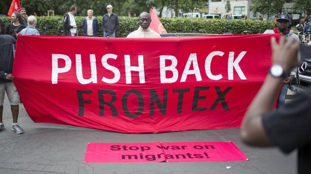 """Aktivisten halten am Weltflüchtlingstag Transparente mit der Aufschrift """"Weiche zurück, Frontex"""" """"Stopp den Krieg gegen Migranten"""" (Berlin, 20.6.15)"""