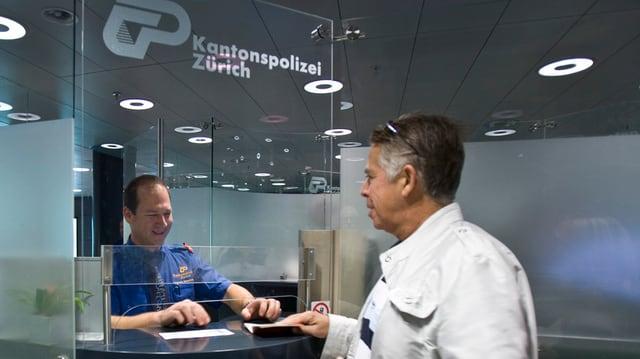 Grenzbeamter am Schalter kontrolliert am Flughafen Zürich den Pass eines Reisenden
