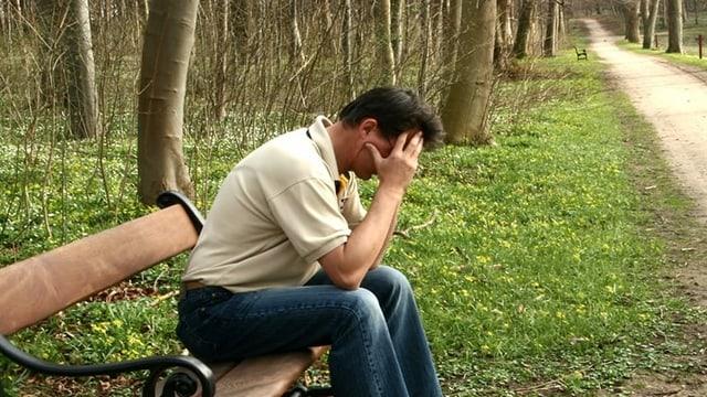 Mann sitzt auf Bank und stützt Kopf in die Hände.