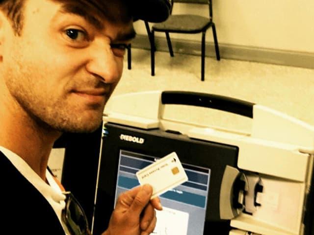 Justin Timberlake vor einem Wahlcomputer stehend macht ein Selfie von sich.