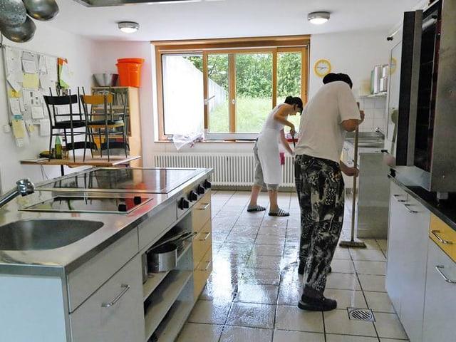 Zwei Menschen putzen Boden in einer grossen Küche.