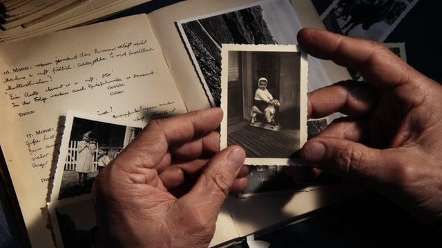 Eine Hand hält ein altes Foto eines kleines Kindes.