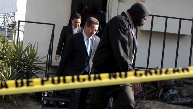 Drei Männer verlassen ein Gebäude.
