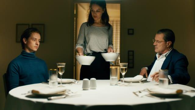 Zwei Männer am Tisch, eine Frau steht mit Tellern in der Hand daneben.