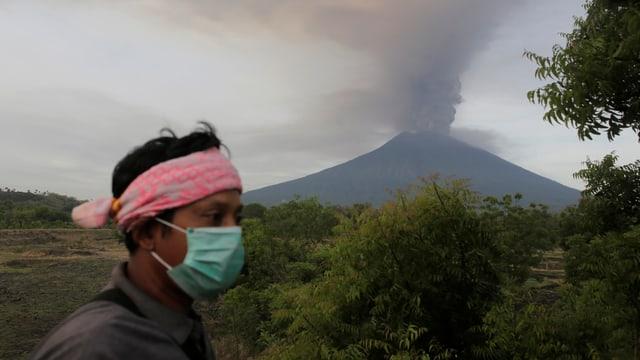 Vulkan Agung bedrohlich nahe: Ein Dorfbewohner von Karangasem schützt sich mit einer Maske