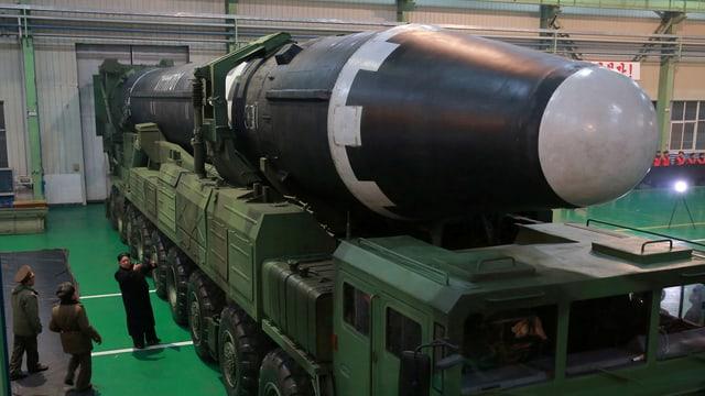 Kim vor einer nordkoreanischen Rakete in einer Fabrik.