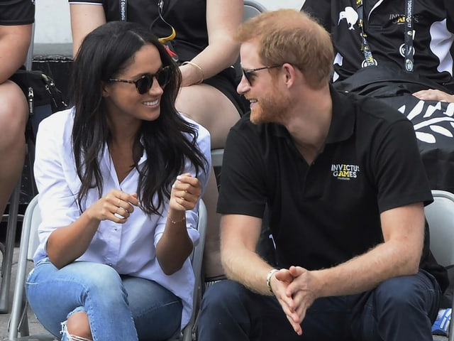 Frau schwarzhaarig und Mann rothaarig sitzen auf Stühlen und unterhalten sich.