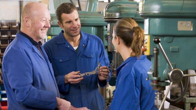 Drei Arbeitende diskutieren in einer Werkstatt