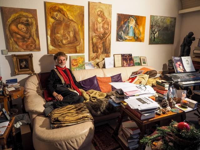 Ernst Sieber sitzt vor einer Bilder-Wand auf einem Sofa.