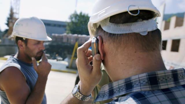 Zwie Bauarbeiter mit Helm, einer hat Handy am Ohr