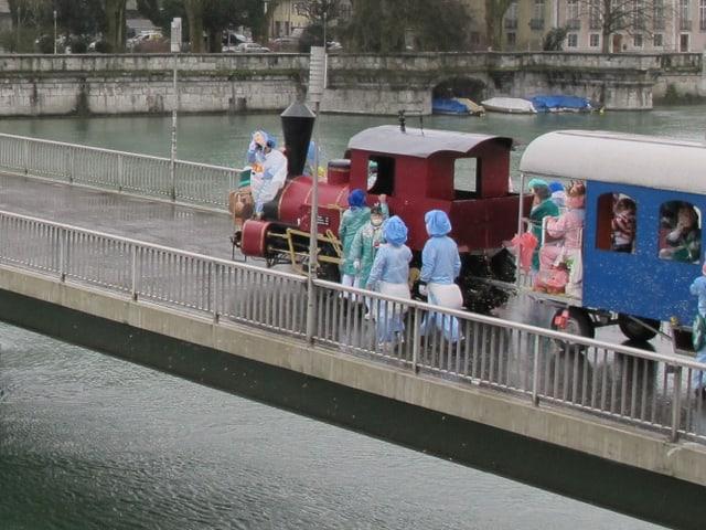 Kleine Fasnachtswagen in Form einer Lokomotive und Waggons überqueren die Fussgängerbrücke.