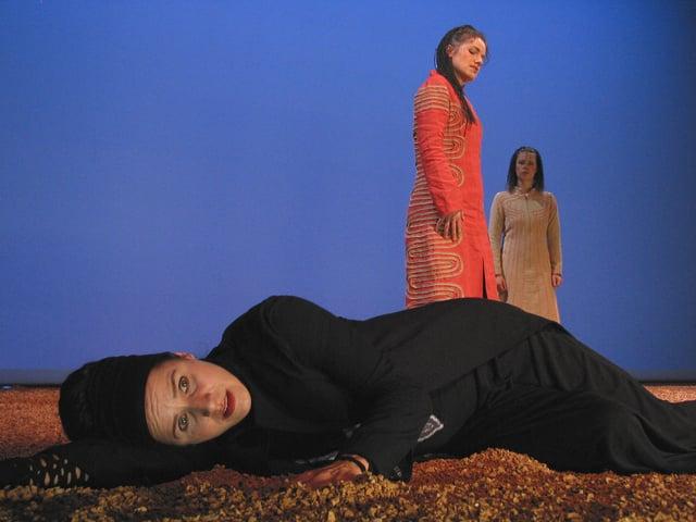 Bühnenszene: Eine Frau in schwarzem Kostüm liegt auf der Bühne, zwei weitere Frauen schauen stehend auf sie herab.