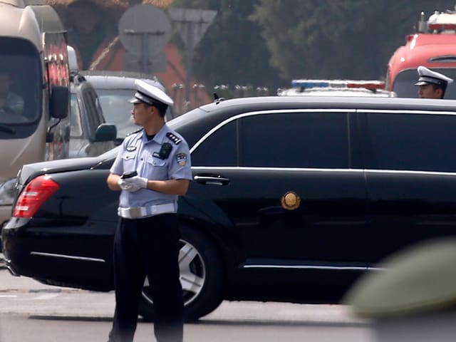 Limousine fährt hinter Polizei vorbei.