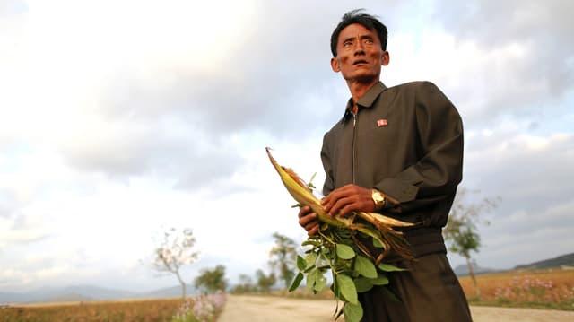 Ein knochiger Mann hält auf einem Feld einen Maiskolben in den Händen