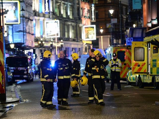 Feuerwehrleute auf einer Strasse.