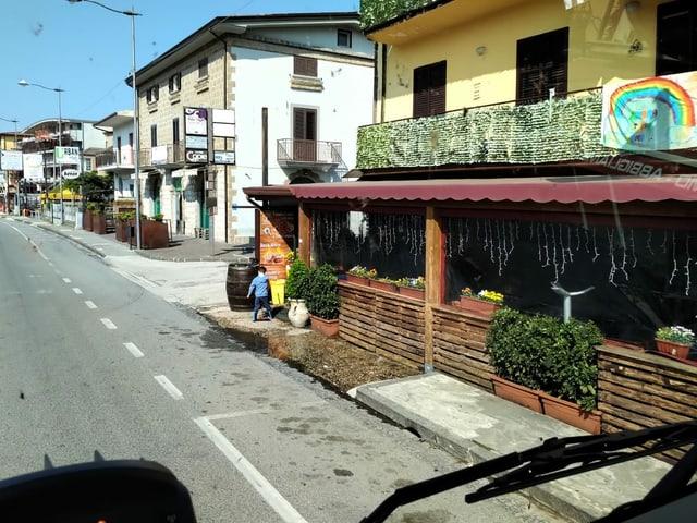 Menschenleere Strasse mit geschlossenen Läden und Bars in Italien.
