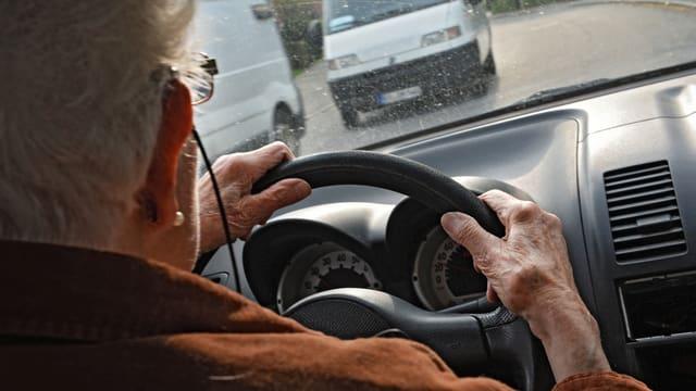 Seniorin sitzt am Steuer ihres Autos.