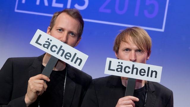 Zwei Männer halten Schilder hoch, auf denen «Lächeln» steht.