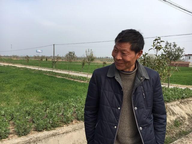 Bauer Hu Chenghai, im Hintergrund sein Land.