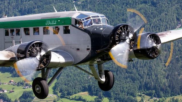 Flugzeug mit drei Propellern in der Luft.