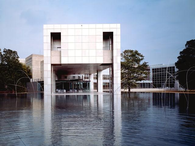 Eckiges. weisses Gebäude, das auf Säulen in einem Teich steht.
