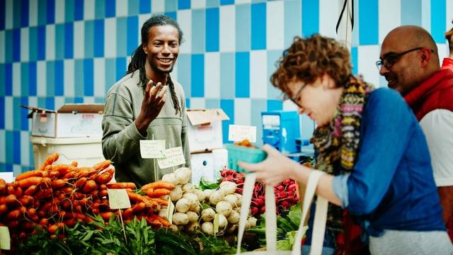 Marktstand mit Verkäufer und einer bunten Auslage von frischem Gemüse.