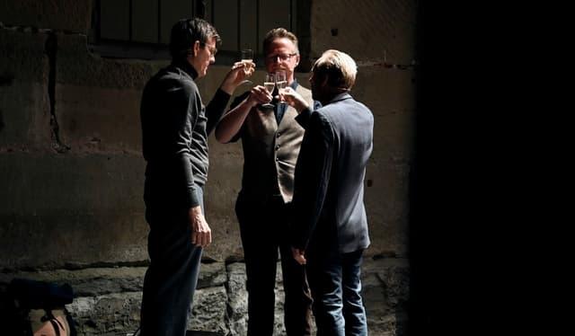drei Männer stossen mit Prosecco an