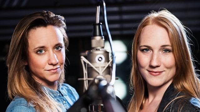 Anna Känzig und Ira May stehen bei einem Mikrophon.