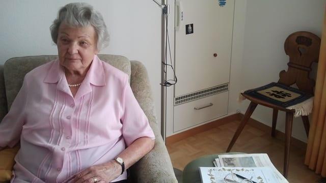 Die Seniorin mit roas Bluse sitzt in einem bequemen Sessel in ihrem Wohnzimmer.