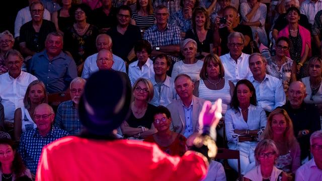 Ein Mann in rotem Mantel und mit Hut von hinten spricht in das Publikum - im Publikum gespannte Gesichter.