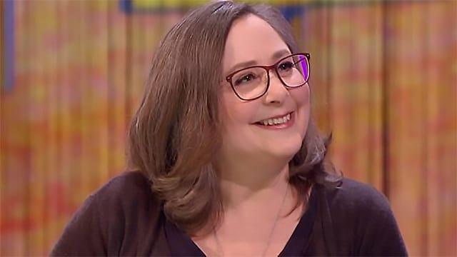 Eine Frau mit braunen Haaren und Brille.