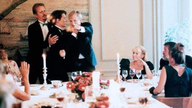 Einige festlich gekleidete Personen stehen um einen Tisch und streiten.