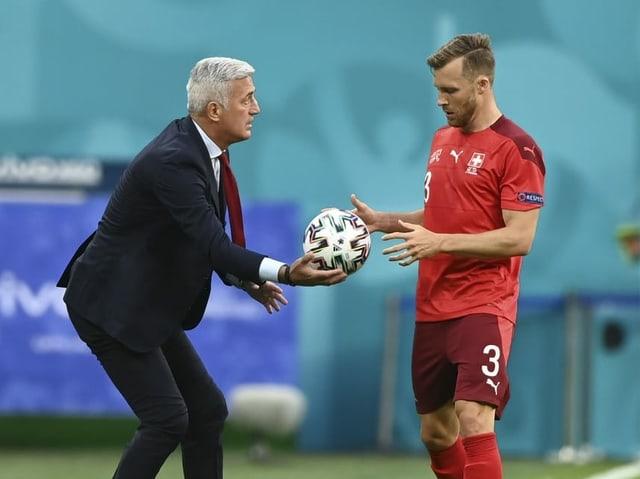 Nati-Trainer Vladimir Petkovic reicht Silvan Widmer an der Seitenlinie den Ball.