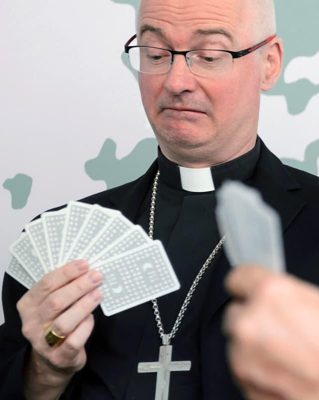 Ein Mann in schwarzem Pfarrersgewand jasst.