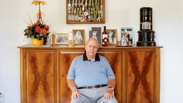 Ein Mann sitzt vor einer Kommode mit Fotos und Erinnerungsstücken.