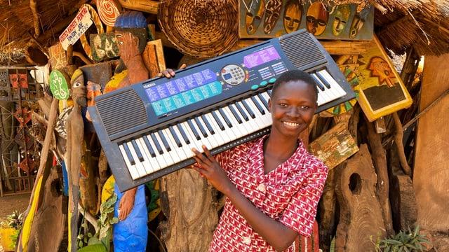ein schwarzes Mädchen hält ein Keyboard in der Hand