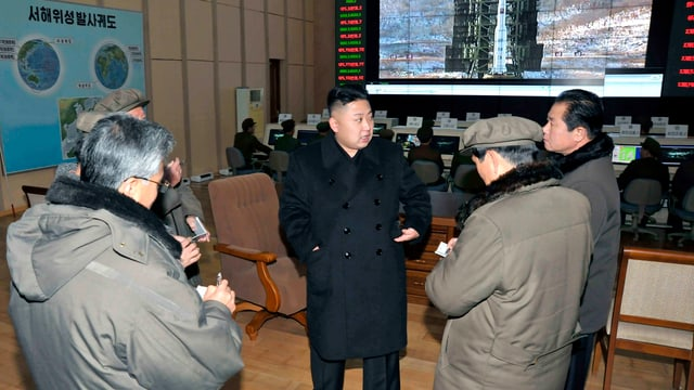 Nordkoreas Führer Kim Jong-Un umringt von Journalisten im Satellitenüberwachungszentrum.