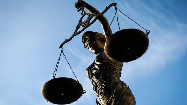 Justizia mit der Waage vor blauem Himmel.