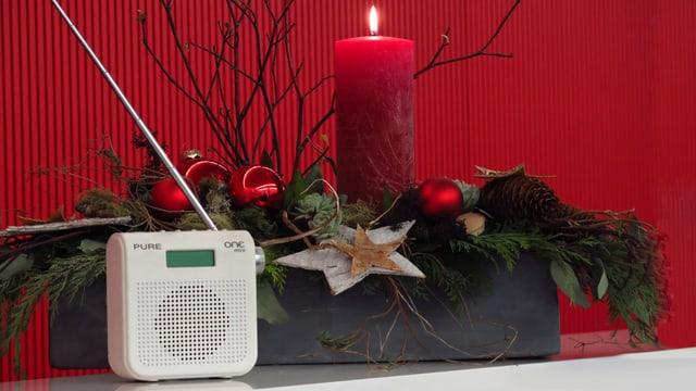 Radiogerät vor einem Weihnachtsgesteck mit brennender Kerze.