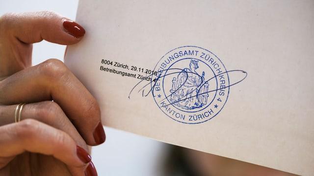 Frau hält Brief mit Betreibungsamt-Stempel in die Kamera.