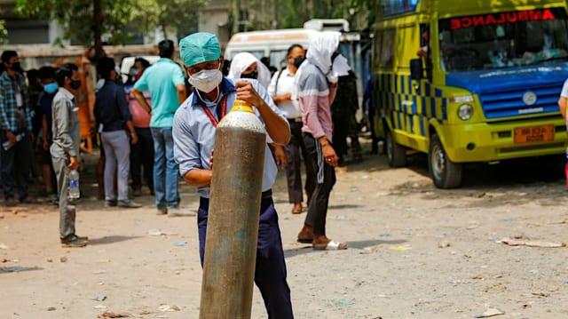 Ein Spitalangestellter trägt eine mannshohe Sauerstoffflasche