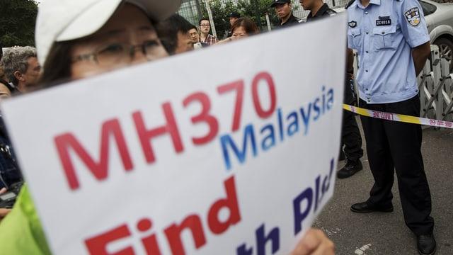 """Angehörige hält an einer Kundegebung ein Schild in die Höhe mit der Aufschrift """"MH370 Find the Plane"""""""